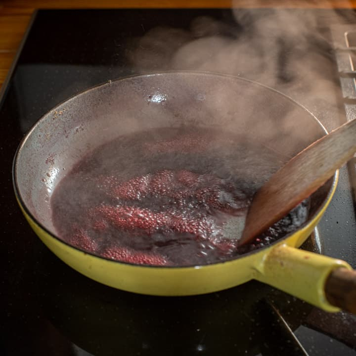 yellow enamel frying pan on a black stove top with red wine boiling and the bottom of the pan being scraped with a wooden spatula