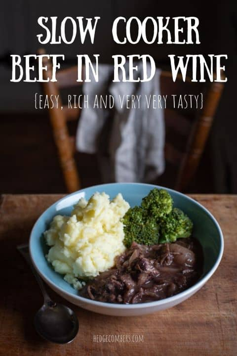 pale blue bowl on wooden kitchen surface filled with mashed potatoes, broccoli and beef in red wine stew