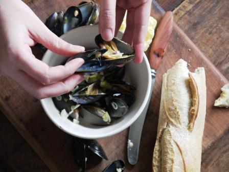 Eating Dairy Free Moules Mariniere from a white bowl on a wooden board with french bread