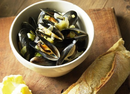 Dairy Free Moules Mariniere in a white bowl with french bread on a wooden board