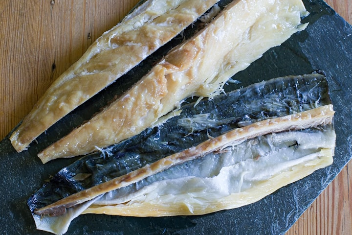 A smoked mackerel fillet on a piece of black slate that has had the skin and bones removed