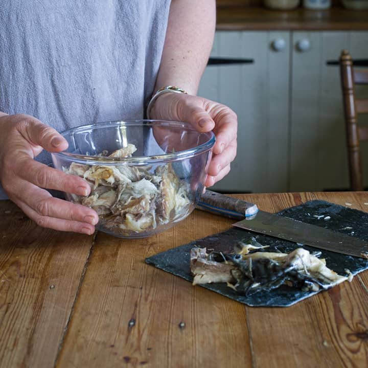 Woman in great holding a glass bowl of smoked mackerel in a rustic wooden kitchen