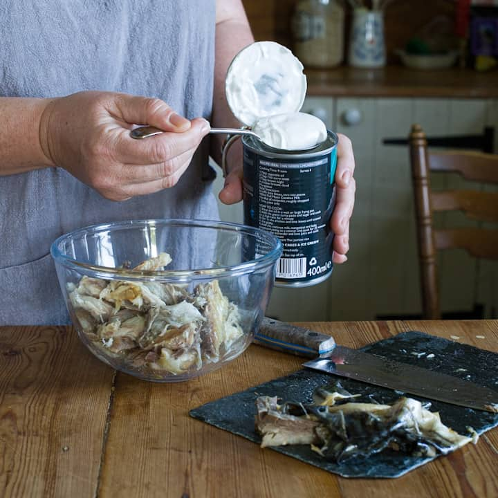 Woman's hands phoning coconut cream from a can of coconut milk into a glass bowl of smoked mackerel fillets