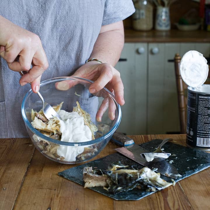 Woman in grey mashing together mackerel pate in a glass bowl on a wooden kitchen counter
