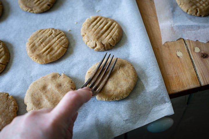 womans hand pressing a fork into ginger cookie dough before baking