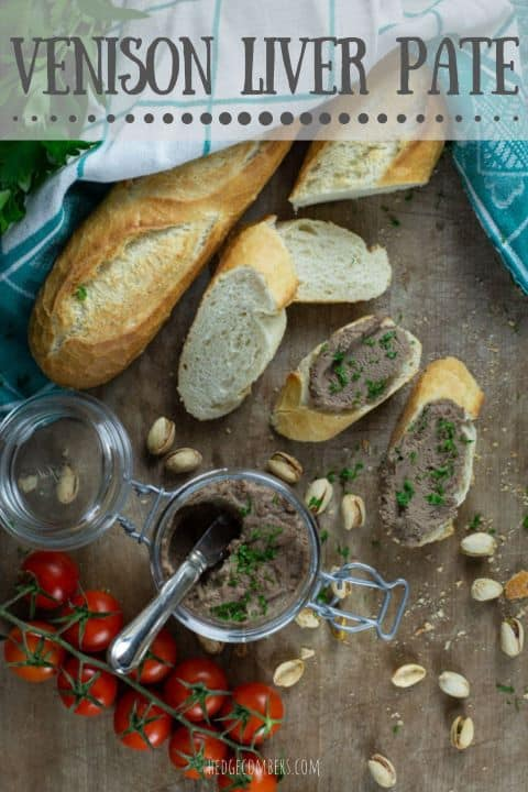 wooden backgrouns with messy supper spread showing sliced baguette, cherry tomatoes, pistachios and a glass jar of homemade pate sprinkled with parsley