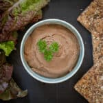small white bowl with liver pate inside, surrounded by lettuce leaves and crackers, on a matte black surface