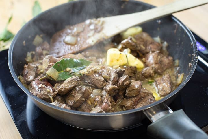 black frying pan with veniosn livers cooking along with bay leaves and onion