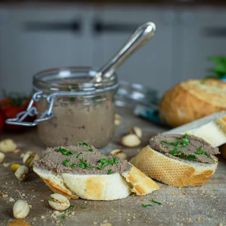 rustic kitchen backdrop with small glass jar of fresh homemade pate, slices of bread and fresh green parsley