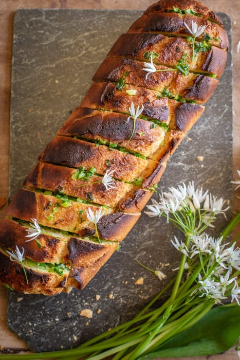 golden brown wild garlic bread fresh from teh oven still wrapped in tin foil with white wild garlic flowers on top