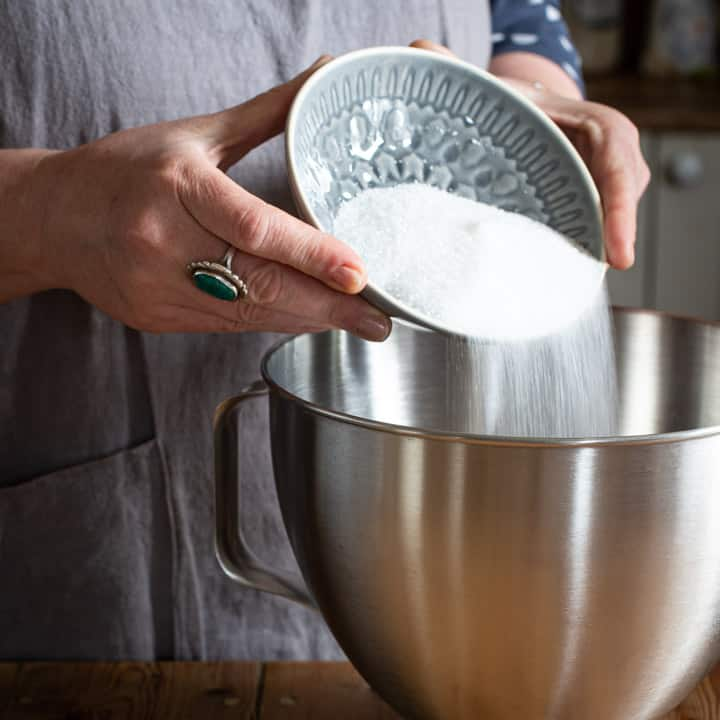 womans hands pouring white sugar from a grey bowl into a large silver mixing bowl