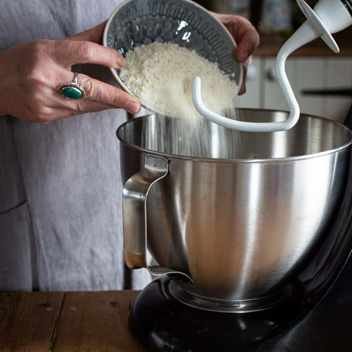 womans hands pouring desiccated coconut into a large silver mixer bowl