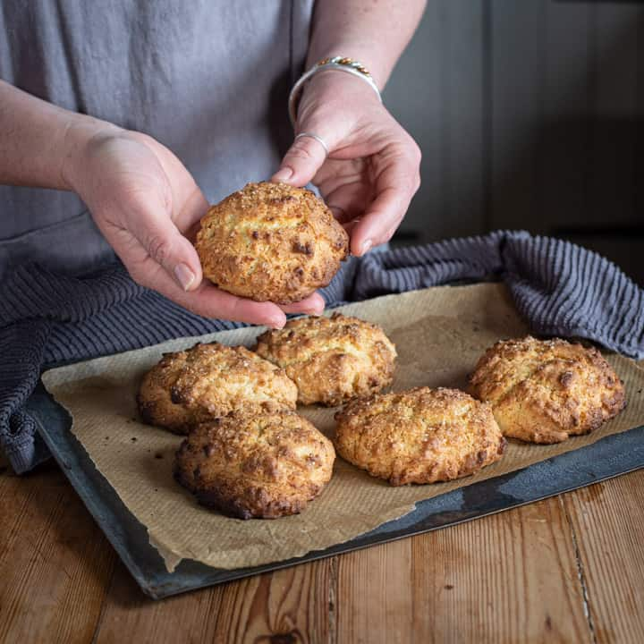 wooden kitchen counter with tray of fresh baked rock cakes and woman holding one rock cake in her hands