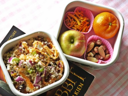Zingy Couscous Salad in a square white bowl with a bowl containg fruit and nuts beside