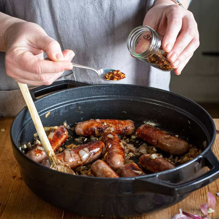 Womans hands spooning chilli flakes from a small glass spice jar into a black cast iron pan of cowboy casserole