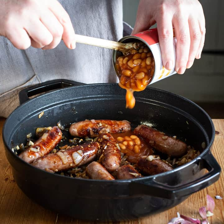 womans hands spooning baked beans from a can into a pan of sausages for a campfire stew