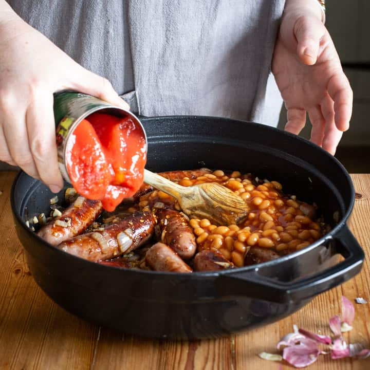 womans hands tipping a can of tomatoes into a black pan of sausage stew