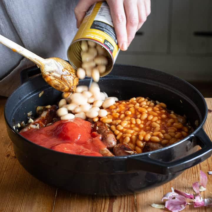 womans hands tipping a can of butter beans into a pan of homemade sausage casserole