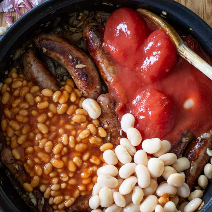 overhead shot of a black pan filled with cooked sausages, canned tomatoes, white beans and baked beans