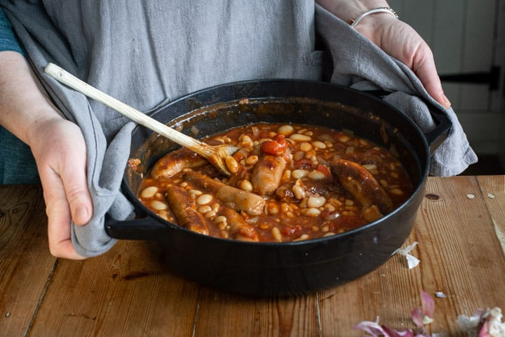 woman holding a small Dutch oven of cowboy sausage stew