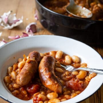 white enamel bowl of sausage and bean cowboy stew on a wooden counter with a black cooking pan and garlic cloves in the background