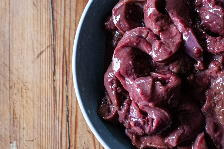 blue bowl on wooden background with ribbons of fresh venison liver inside