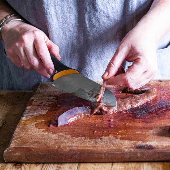 womans hand using knife to remove tough membranes from fresh venison liver to make pate