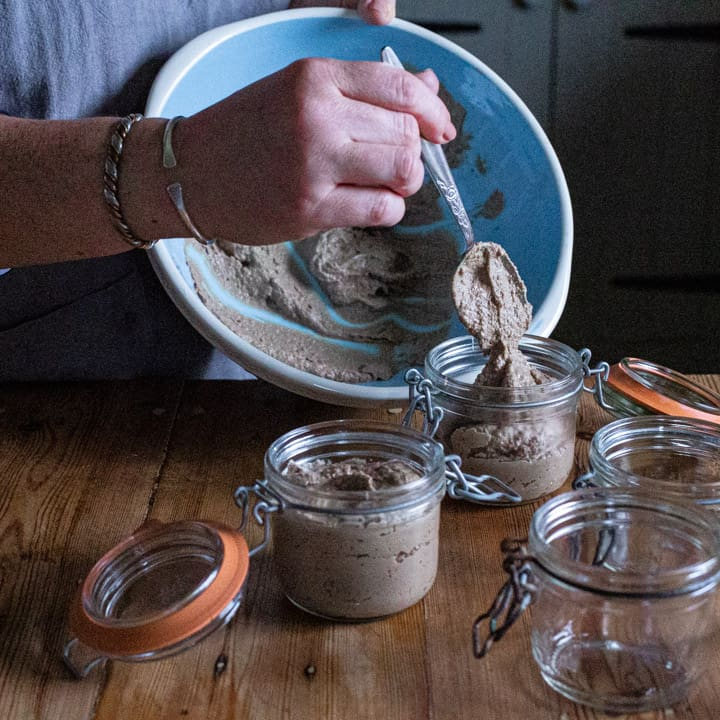 womans hands spooning warm pate from large blue bowl into small glass Kilner jars