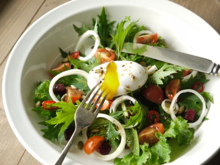 Poached Duck Egg Salad in a white bowl with a knife and fork