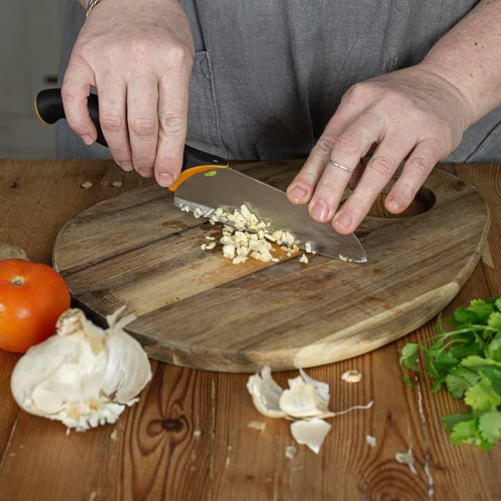 womans hands chopping fresh garlic on a wooden chopping board