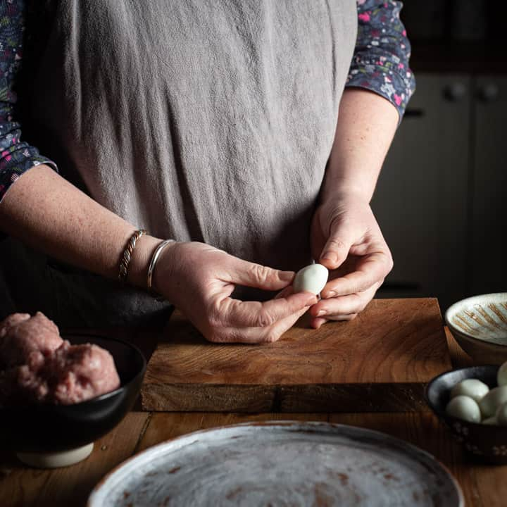 womans hands holding a small quails egg on a rustic wooden kitchen counter