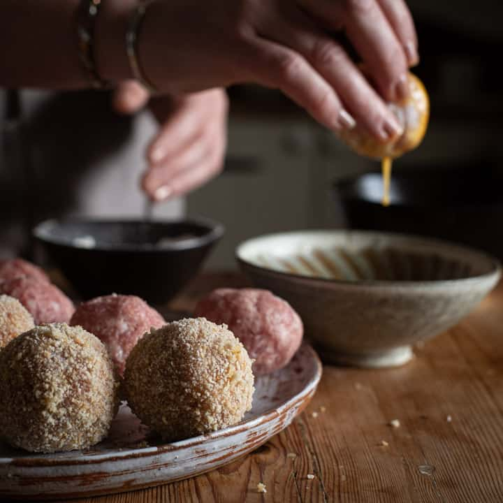 wooden kitchen counter and tray of scotch eggs being made with hands in background lifting a scotch egg out of eggwash