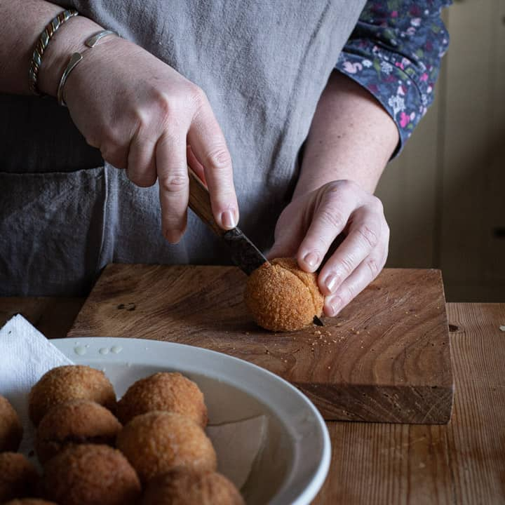womans hands cutting a scotch egg in half on a wooden chopping board with white bowl of more eggs close by