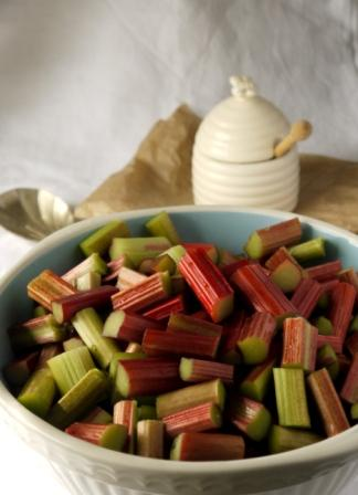 Rhubarb in a bowl beside a pot of honey ready to make Rhubarb Strawberry and Almond Crumble