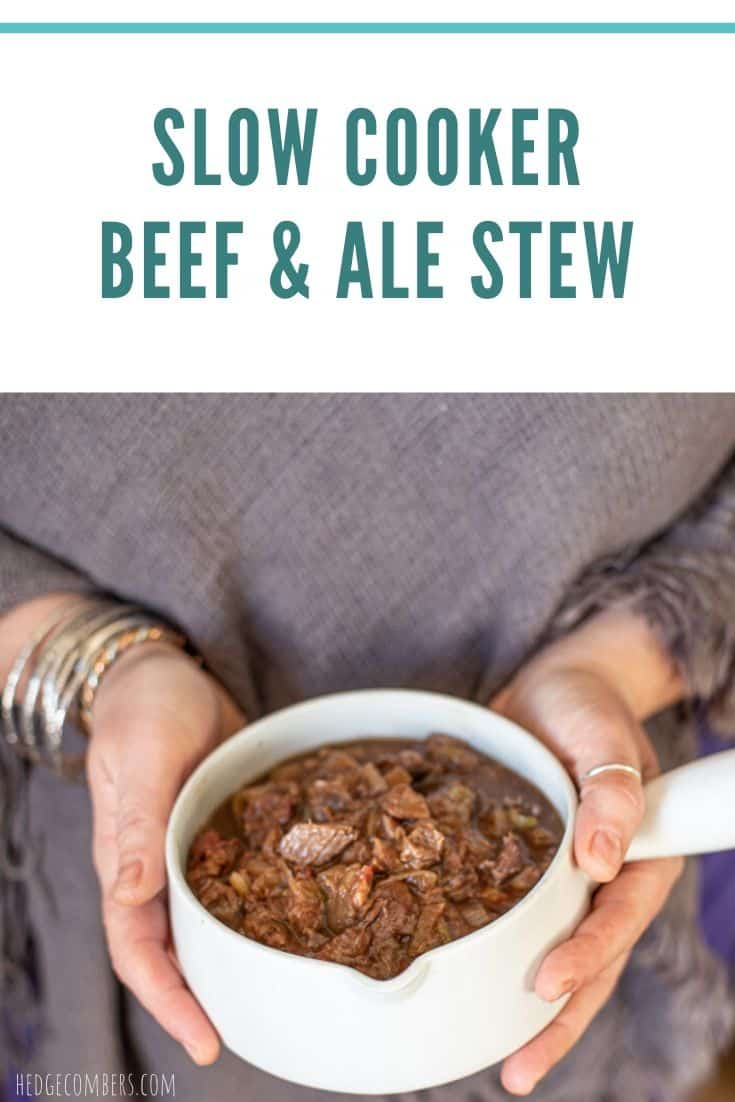 womans hands holding white pot of beef and ale stew against a grey jumper