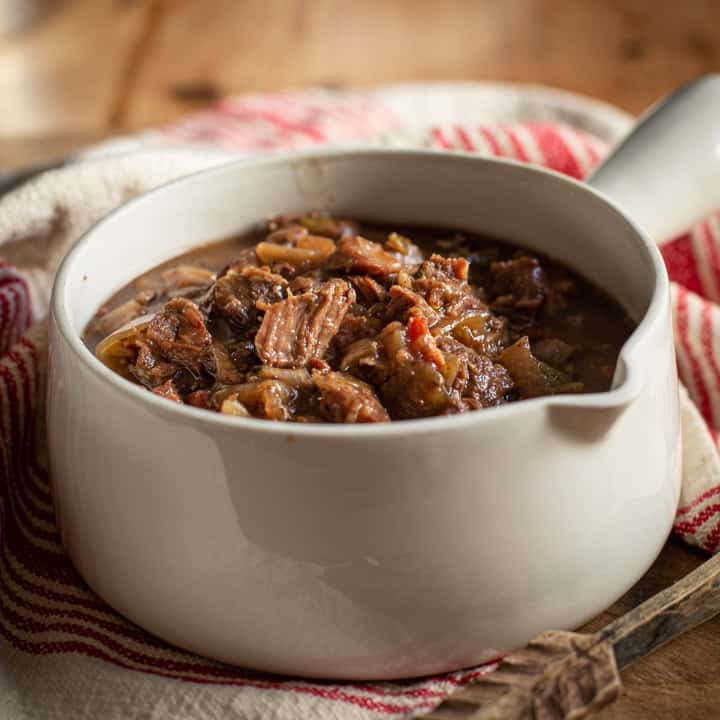 beef and ale stew in white pot with wooden background and wooden spoon