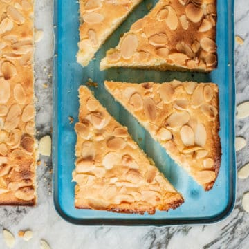freshly baked almond slice on blue packed lunch box lid