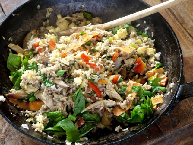 Chicken and Health Egg Fried Rice in a wok with a wooden spoon