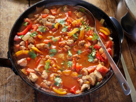 Paprika Pork Fricassee in a large skillet with a serving spoon on a wooden table