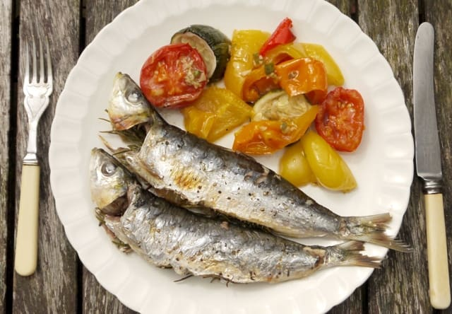 2 Cornish Sardines on a white plate with roasted vegetables with a knife ans fork on a wooden table