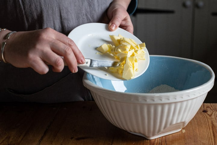 womans hands scraping butter from a white plate into a blue mixing bowl on a wooden kitchen counter