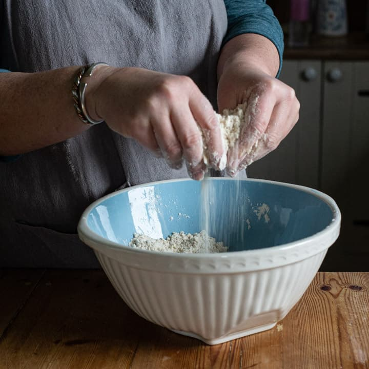 womans hands rubbing butter into flour in a blue mixing bowl on a wooden kitchen counter