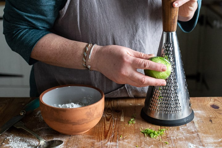 womans hands grating a lime on a wooden kitchen counter