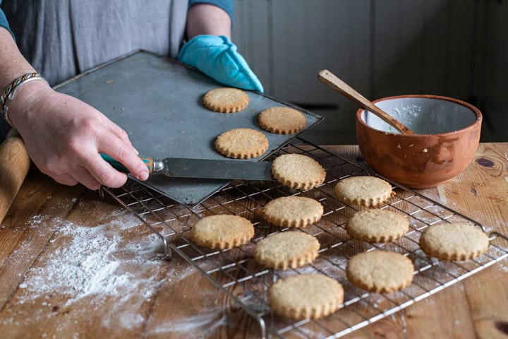 womans hands moving hot freshly baked cookies from a baking sheet onto a wire cooling rack