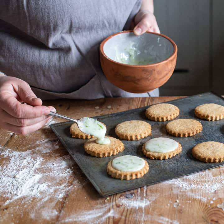 womans hands spooning icing onto fresh cookies on a baking sheet