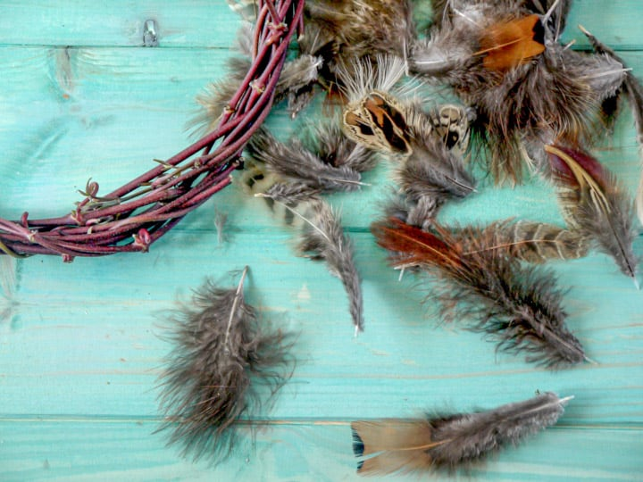 hand made pheasant feather wreaths against a blue wooden background