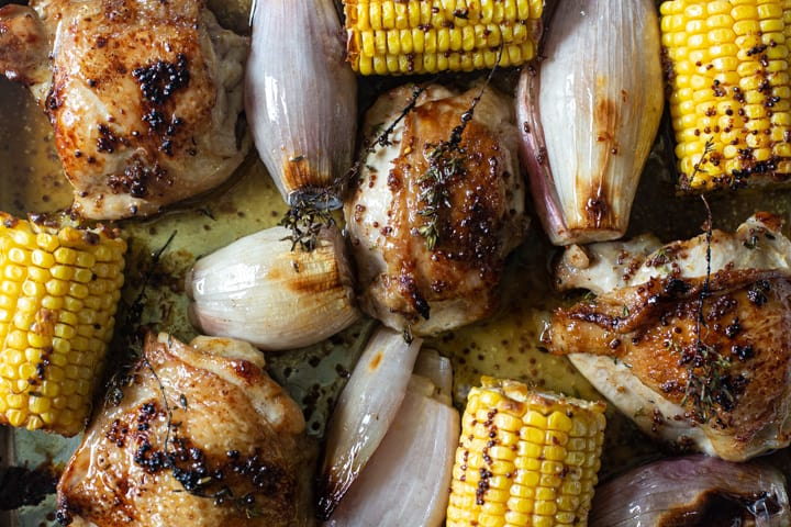 close up of sheep pan chicken thighs with corn on the cob and shallots