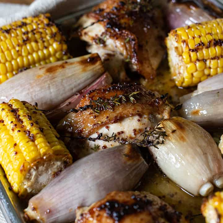 inside of a baking tin of oven baked corn, shallots and chicken thighs
