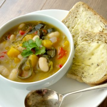 Deep bowl of veggie pumpkin and butterbean stew served with bread and butter