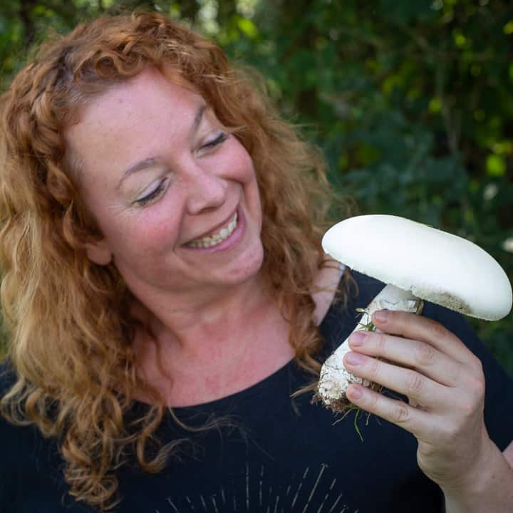 Smiling woman holding a wild horse mushroom